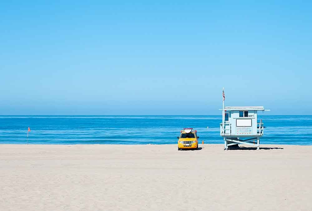 Lifeguard station on beach with yellow car